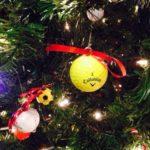 Man decorates tree with golf balls